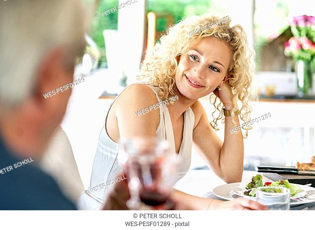 Smiling young woman having meal with family