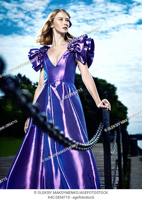 Artistic fashion portrait of a young beautiful woman in a beautiful long evening gown standing at a pier