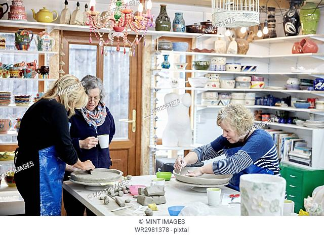 Three women in a pottery studio working with clay