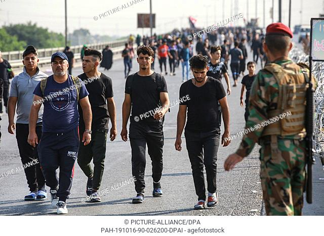 16 October 2019, Iraq, Baghdad: A member of the Iraqi security forces (R) observes Shia Muslims march from Baghdad to visit the the Husayn Mosque in Karbala on...