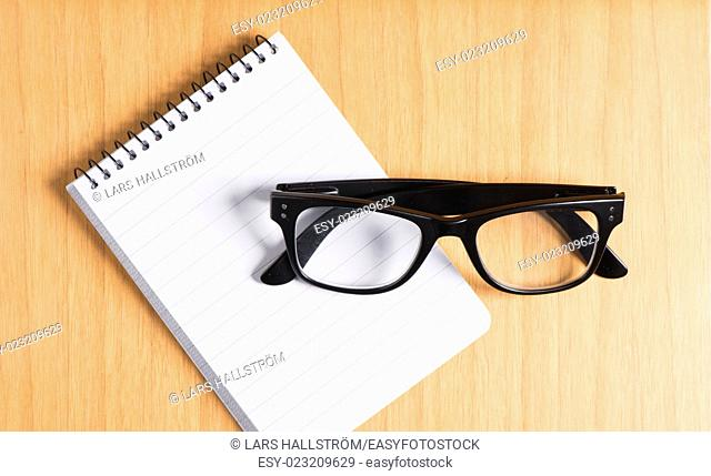 Black glasses and notepad on wooden office table. Concept of education, work and writing notes