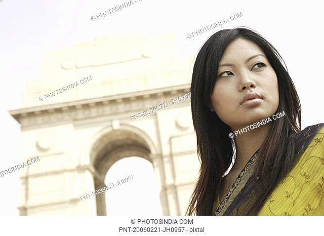 Low angle view of a young woman in front of a monument, India Gate, New Delhi, India