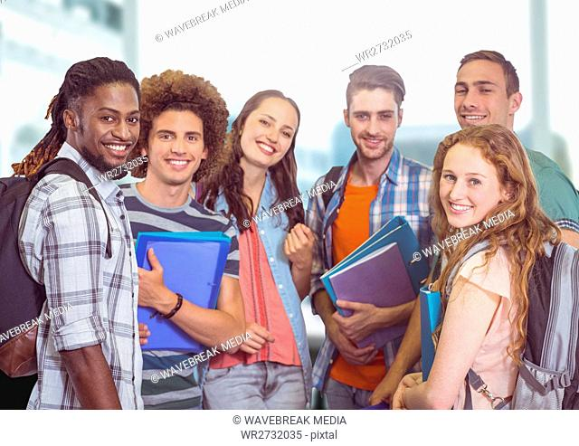 Students group smiling at camera against a light background