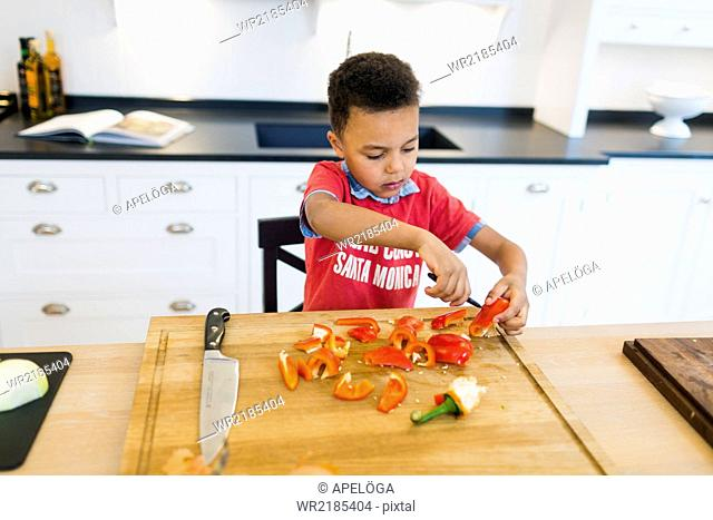 Boy chopping red bell pepper in kitchen