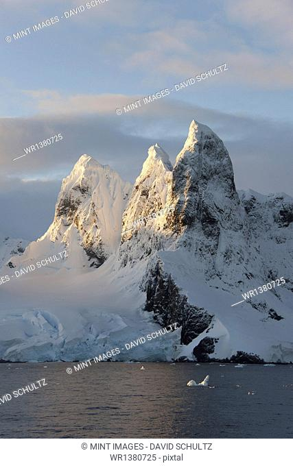 Sunrise on the mountain tops at the north entrance to the Lemaire Channel along the Antarctic Peninsula