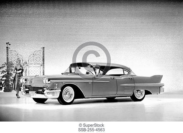Woman walking behind a 1958 Cadillac Series 62 Sedan