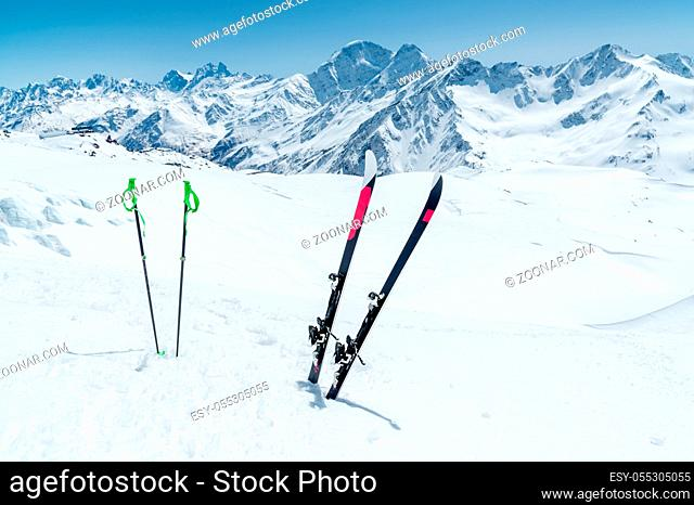 A pair of skis and ski poles stick out in the snow on the mountain slope of the Caucasus against the backdrop of the Caucasian mountain range and the blue sky...