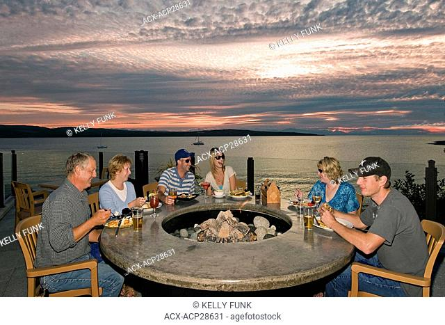 Friends and family enjoy a brilliant evening while dining at an oceanside restaraunt in Powell River, on the Sunshine coast of the Vancouver coast and mountain...