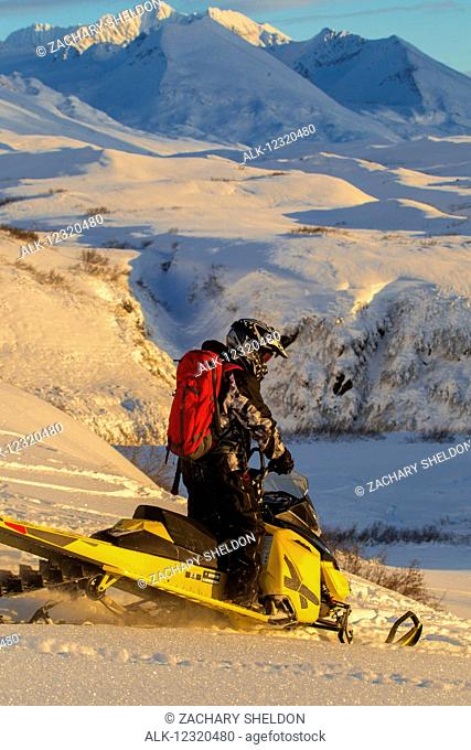 Snowmobiler on the slopes of Thompson Pass at sunset, Southcentral Alaska, USA