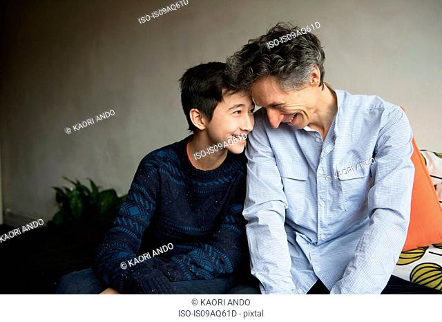 Teenage boy and father face to face on sofa