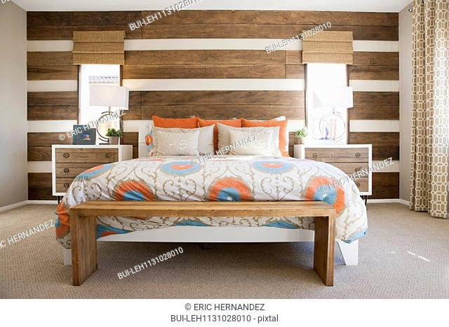 Cozy and tidy bed with wood paneled wall in contemporary bedroom; Moreno Valley; California; USA