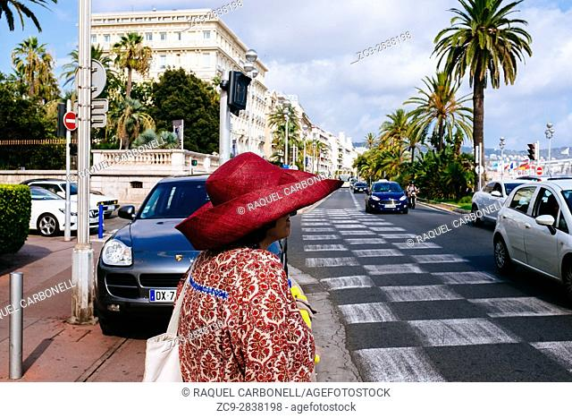 Woman wearing elegant hat and clothes standing in Promenade des Anglais. Nice, Alpes-Maritimes, French Riviera, Provence-Alpes-Côte d'Azur, France