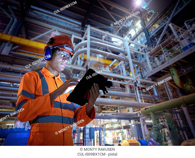 Composite image of engineer in nuclear power station using digital tablet