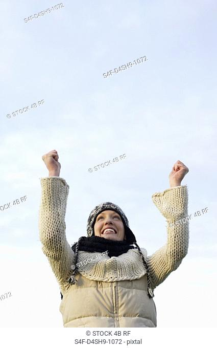 Young woman with scarf and cardigan under the sky, close-up