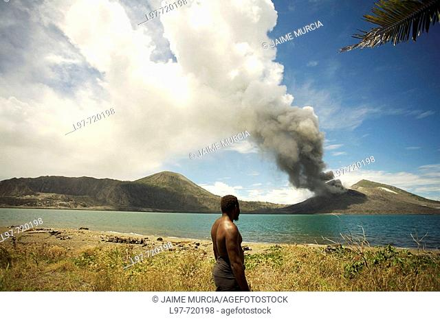 Local villager watching Tavuvur volcano in the distance, from Matupit island, Rabaul East New Britain, PNG