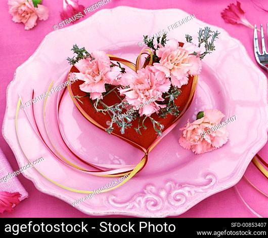 Arrangement of pink carnations and rosemary in a red heart