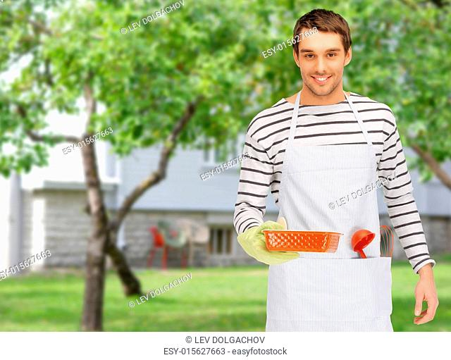 people, cooking, culinary and food concept - happy man or cook in apron with baking and kitchenware over summer garden and house background