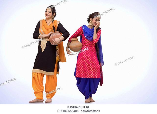 Two woman carrying a Earthen Pot