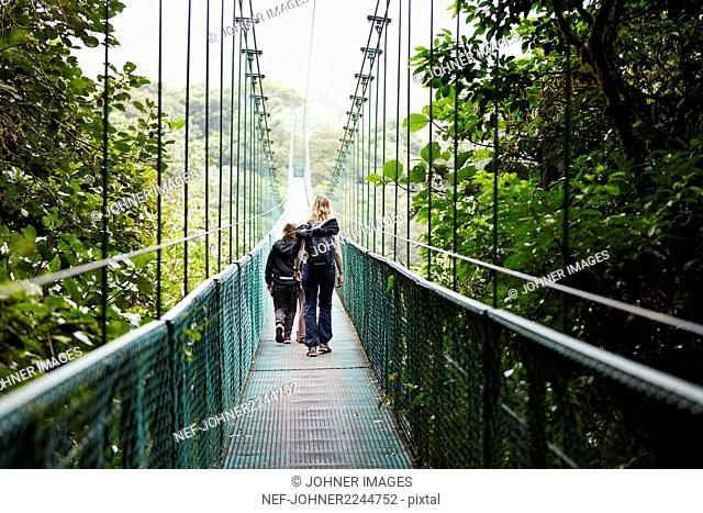 Mother with daughters on hanging bridge