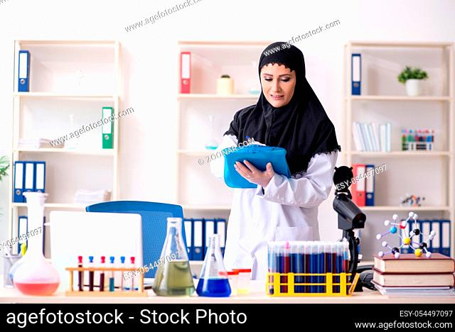 The female chemist in hijab working in the lab