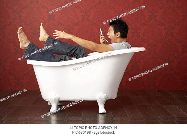 Man Playing with his Mobile in the Bathtub, Korea