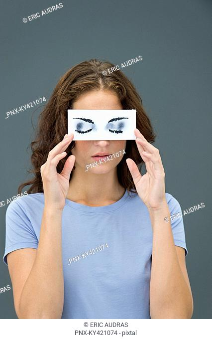 Woman hiding behind paper with false eyes