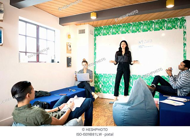 Young businesswoman presenting in creative meeting room