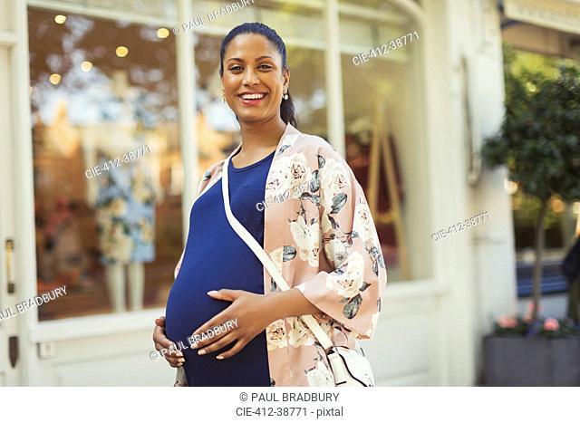 Portrait smiling, confident pregnant woman outside storefront