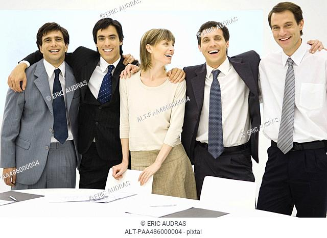 Team of business associates standing with arms around each other, smiling, group portrait
