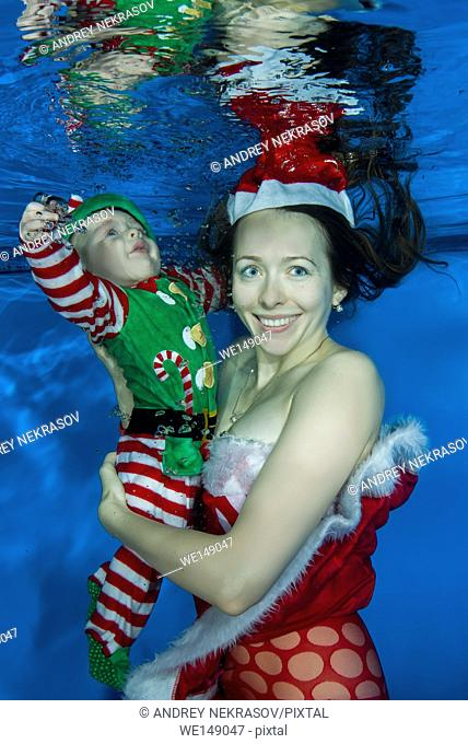 Mom dressed as Santa and a boy dressed as Santa's helper posing under the water in the pool