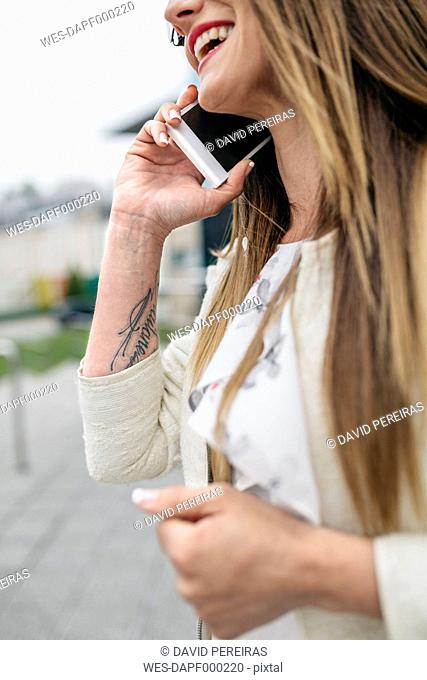 Happy woman with tatoo in arm on cell phone