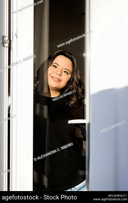 Thoughtful woman with down syndrome smiling while looking through window at home