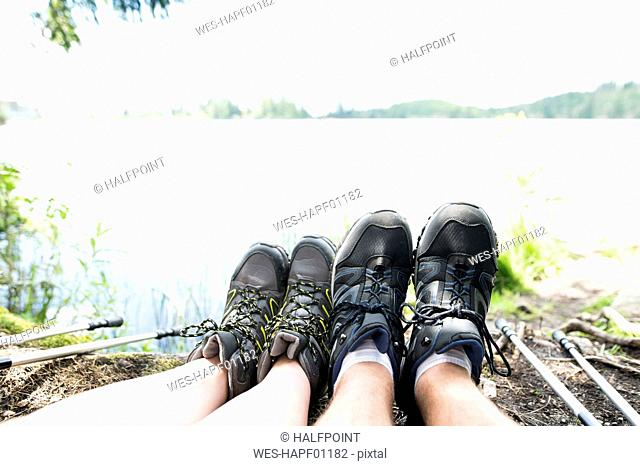 Legs of couple on a hiking tour resting at a lake