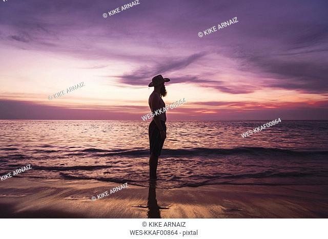 Thailand, Phuket, silhouette of man wearing hat standing at seaside by sunset