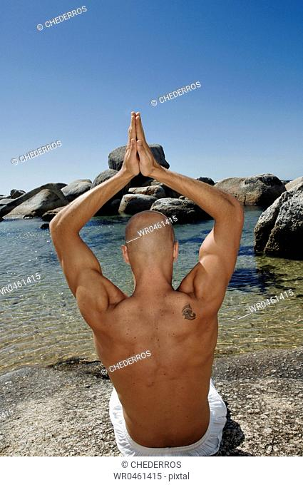Rear view of a young man practicing yoga
