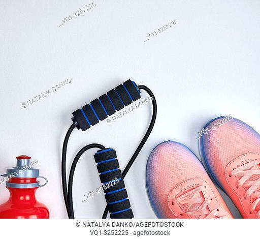 pair of pink sneakers with laces on a white background, top view, copy space