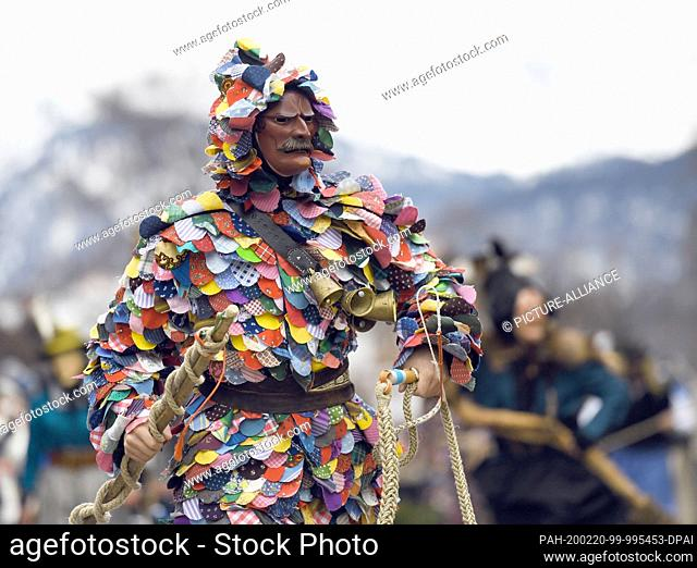 20 February 2020, Bavaria, Mittenwald: Musicians and other traditional figures parade through the village behind the Mittenwald bell stirrers during the...