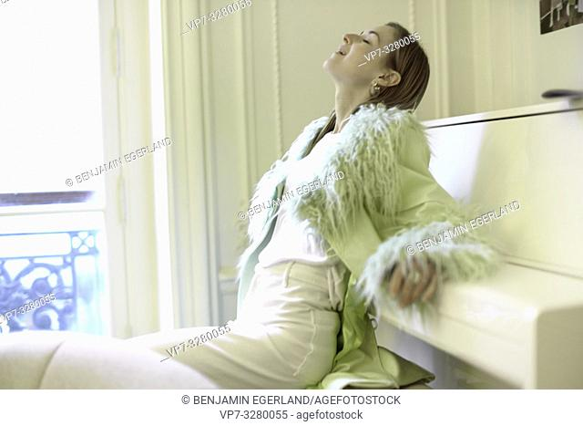 sophisticated aristocratic woman leaning on piano at home, in Paris, France