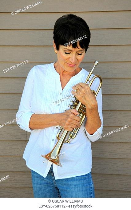 Mature female beauty holding her trumpet outside