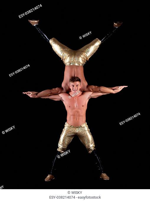 Pair of muscular half-naked acrobats posing in studio