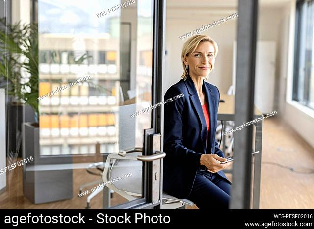 Portrait of blond businesswoman holding tablet in conference room