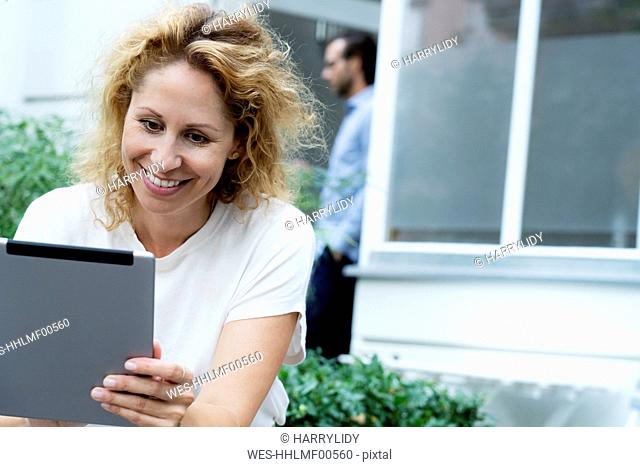 Laughing woman working on her digital tablet, sitting in the garden