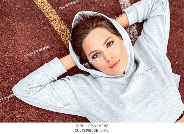 Portrait of young woman lying on sports track, overhead view