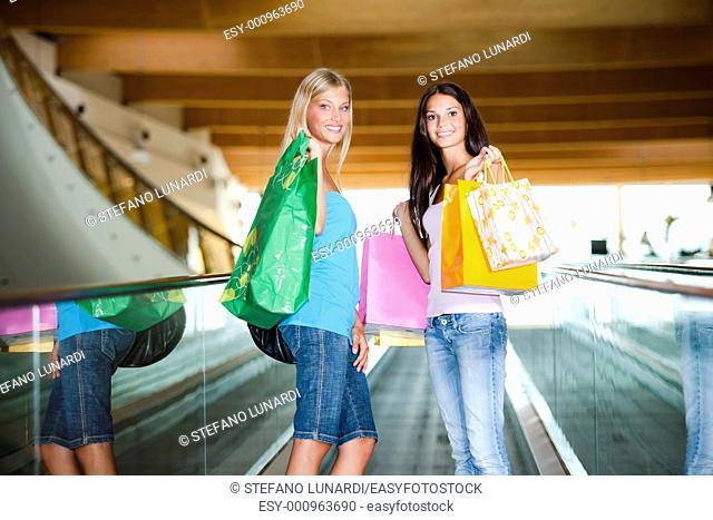 Beautiful teenage girls on escalator at shopping center