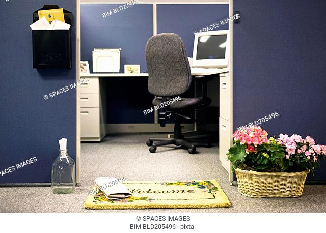 Flowerpots and welcome mat in front of cubicle
