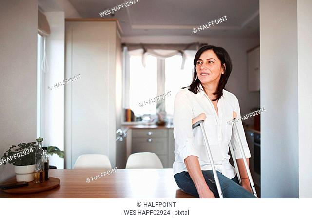 Mature woman with crutches, alone at home