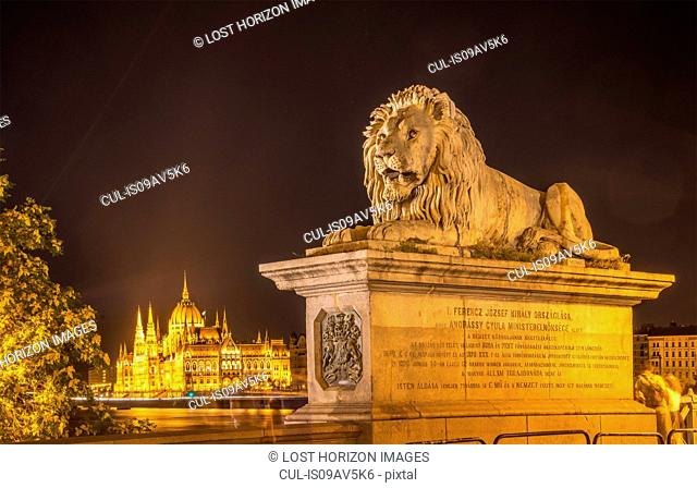 Lion Statue on Chain Bridge, the Parliament in background, at night, Hungary, Budapest