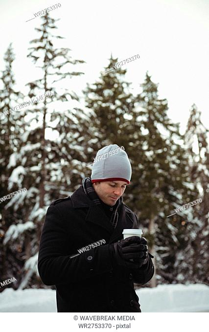 Man in warm clothing holding coffee cup