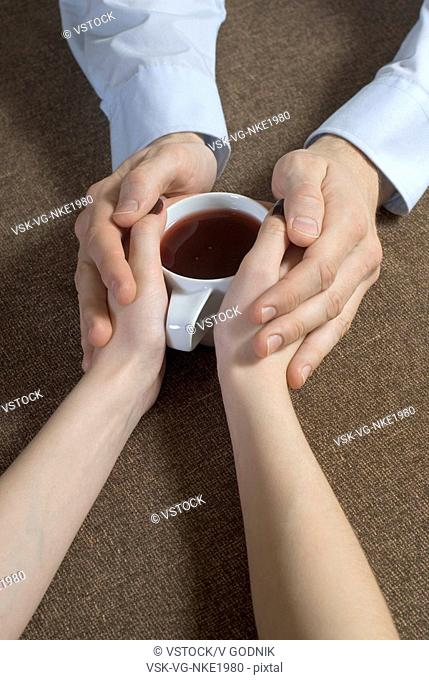 Close-up of young couple hand's holding tea cup together
