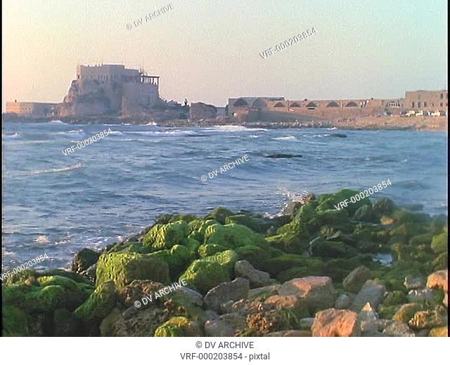The sea crashes against the shore near ancient Roman ruins